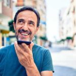 Kundenzufriedenheit messen und steigern - Beitragsbild Kontakt aufnehmen mit unzufriedenen Kunden - Mann mit Smartphone am telefonieren und lächelt