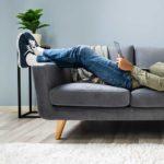 NPS-Stichprobengröße - Beitragsbild Facebook - Mann liegt auf der Couchh mit einem Laptop und berechnet den NPS