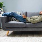 NPS-Stichprobengröße - Beitragsbild - Mann liegt auf der Couchh mit einem Laptop und berechnet den NPS